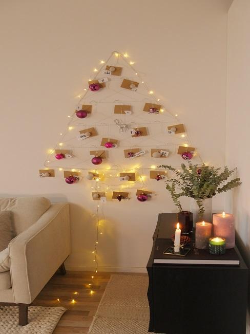 Ein Wohnzimmer mit Sofa und Sideboard, gemütlicher Kerzendeko und einem aus Licherketten geformten Weihnachtsbaum an der Wand