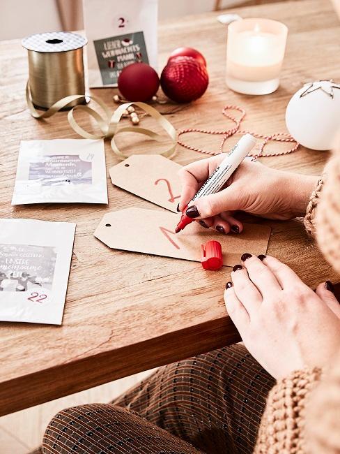 Eine Frauenhand schreibt Nummern auf Papier Etiketten an einem Holztisch zum Adventskalender Basteln