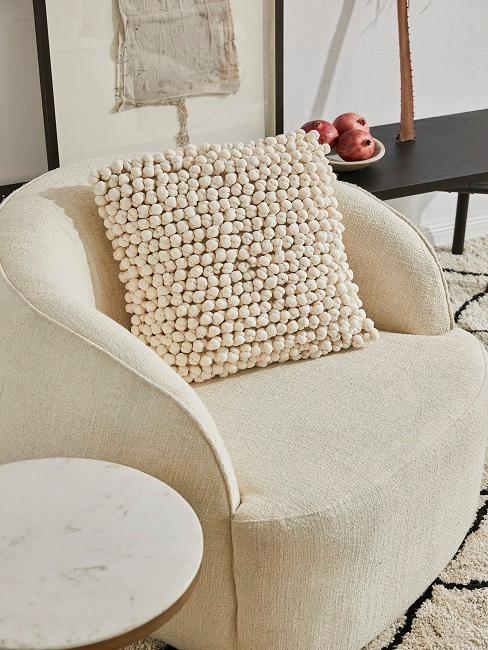 Ecrufarbenes Kissen auf ecrufarbenem Sessel