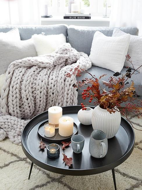 Coffee table with autumn decorations in front of a gray couch
