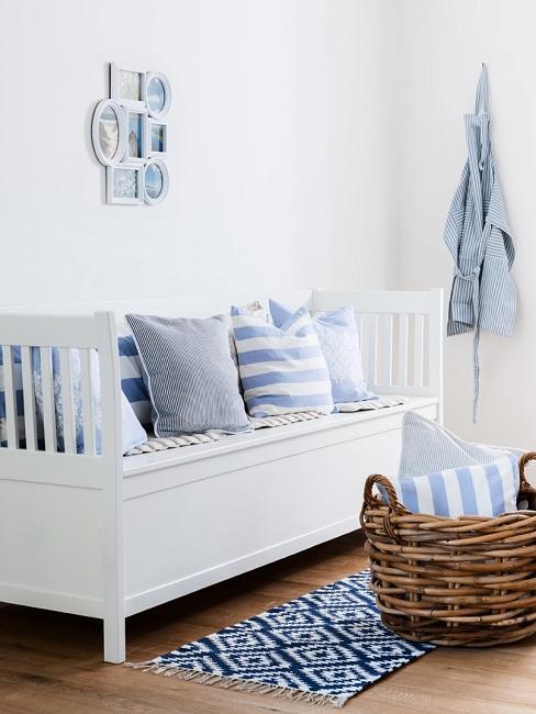 Eine weiße Landhausstil-Sitzbank mit Kissen in maritimem Weiß-Blau