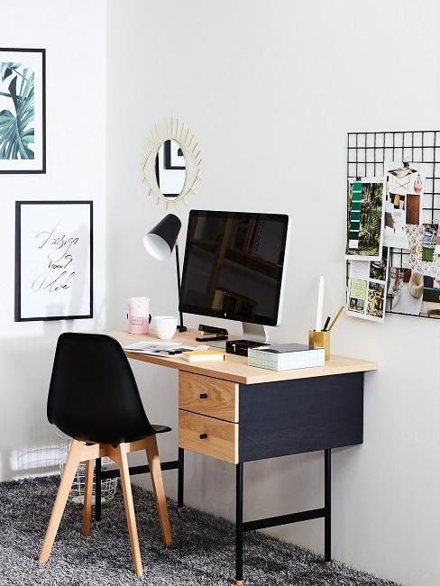 Arbeitsplatz in schwarz und hellem Holz mit Wandbildern und Pinnwand