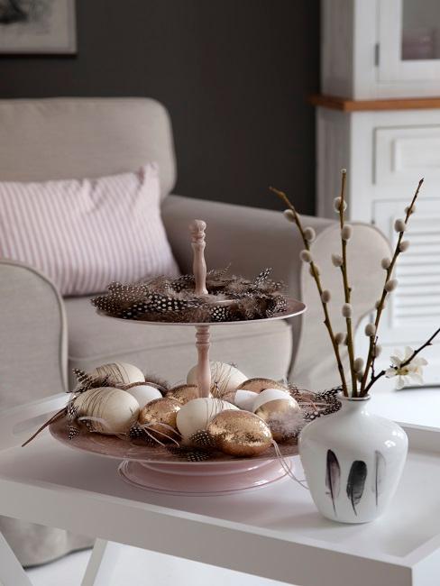 Couchtisch mit Etagere mit Ostereiern neben einer Vase