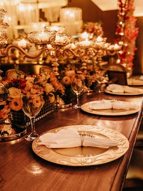 Klassische Tischtafel aus Holz mit Kerzenleuchtern und viel Blumen zur Silvesterdeko