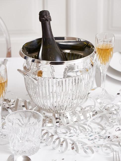Silberner Sektkühler mit Flasche auf einem Tisch mit weißer Tischdecke, darauf silbernes Konfetti und Luftschlangen sowie Kristallgläser