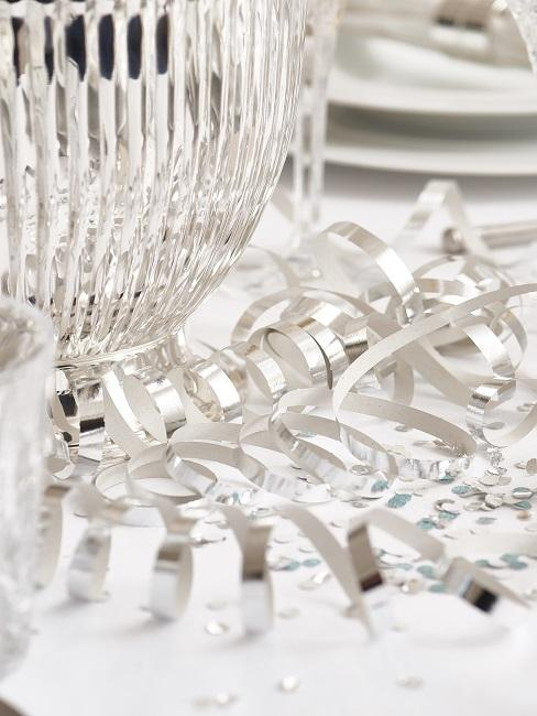 Gedeckter Tisch mit Luftschlangen und Konfetti in Silber auf einer weißen Tischdecke als Silvester Inspiration