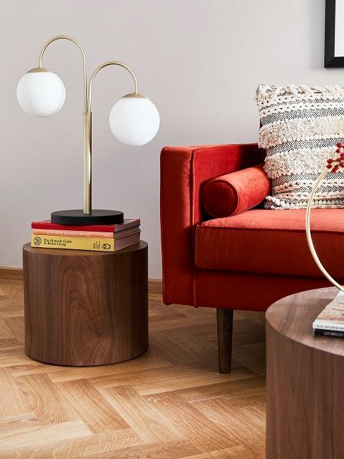Rotes Sofa neben Tisch mit Büchern und Lampe