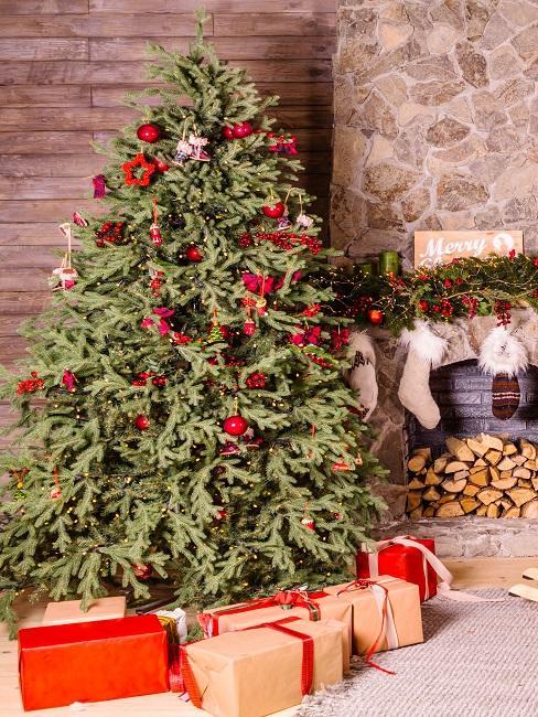 Ein geschmückter Weihnachtbaum mit vielen geschenken drumrum neben einem Kamin