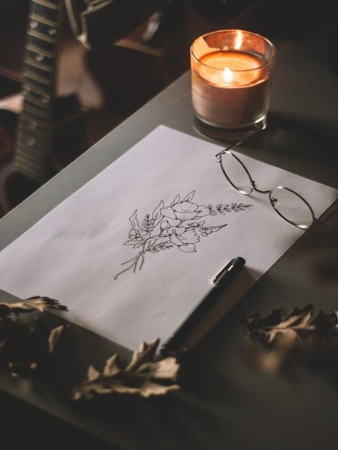 Ein Blatt mit floraler Zeichnung auf einem Tisch mit Brille, Stift und Kerze