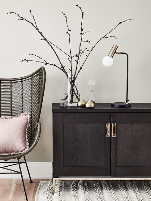 Dunkelbraune Holz Kommode mit einer Vase mit Zweigen und einer Tischlampe dekoriert