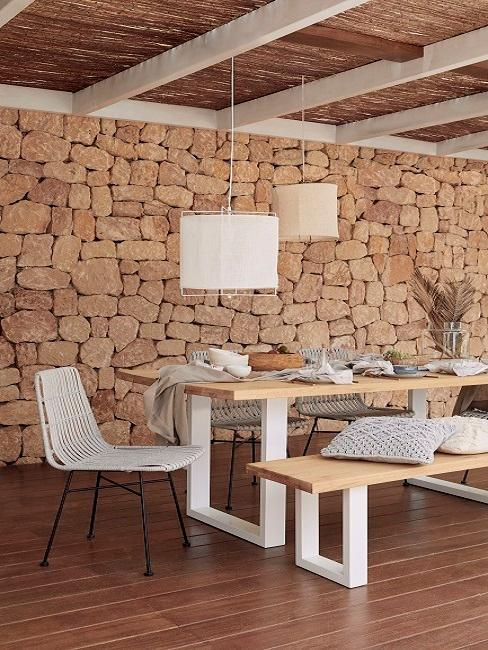 Ibiza Style Esszimmer mit Steinwand, Holztisch und weißen Stühlen