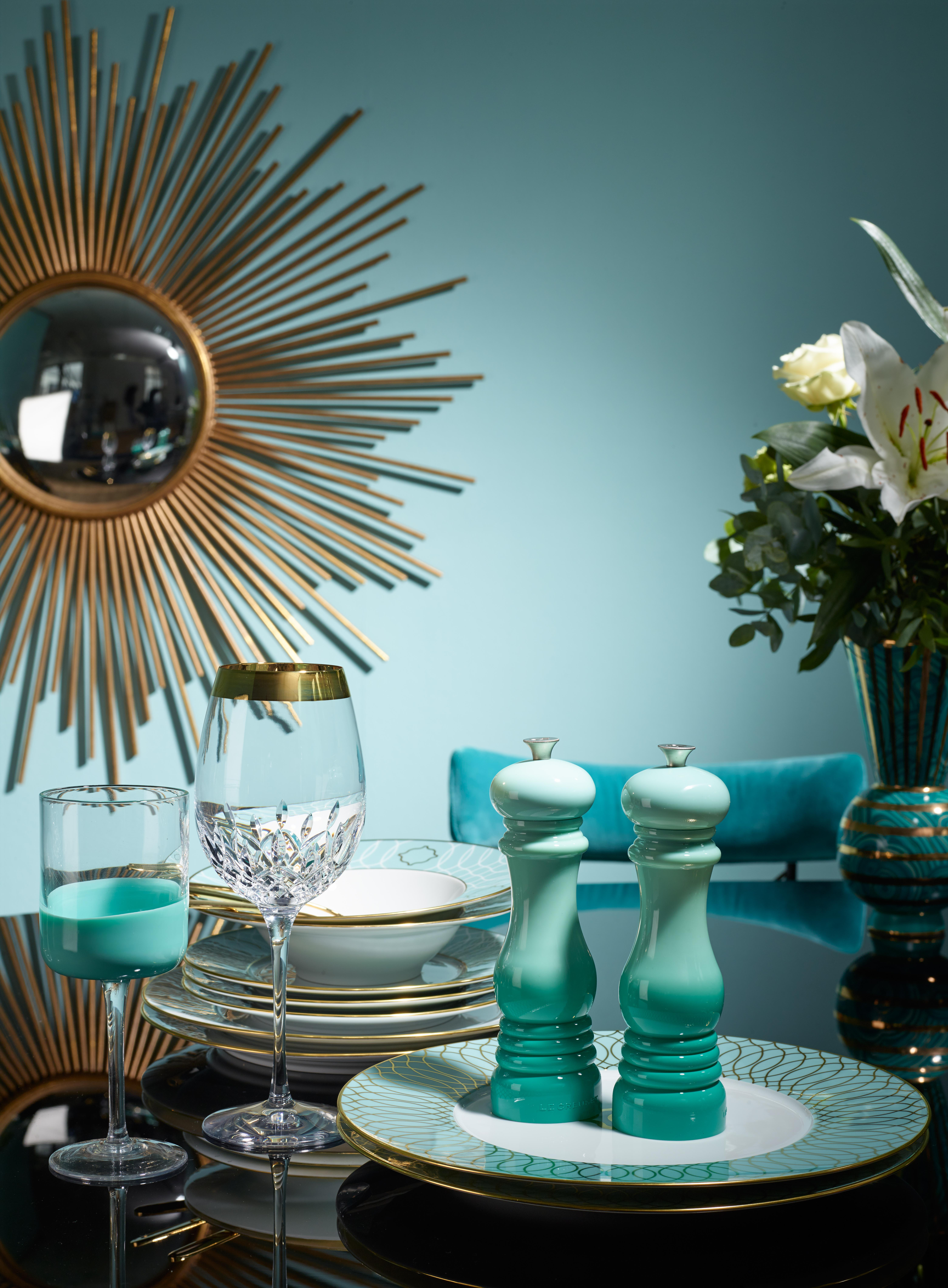 Turquoise wall with golden sun mirror, in front of it a set table with dishes and glasses with gold details