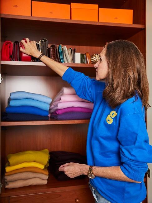 Ordnung im Kleiderschrank farbig sortierte Kleidung durch Frau