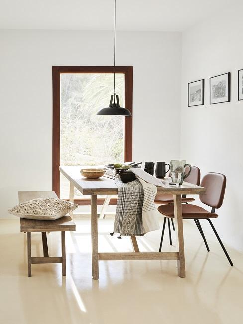Kleines Esszimmer einrichten mit Holztisch und hellen Kissen und Decke