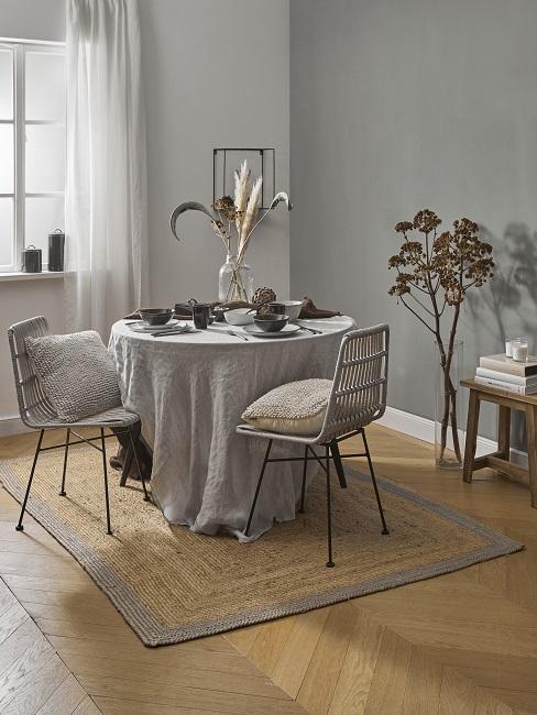 Kleines Esszimmer einrichten mit rudem Tisch mit Deko, Teppich aus Jute und Stühlen aus Rattan
