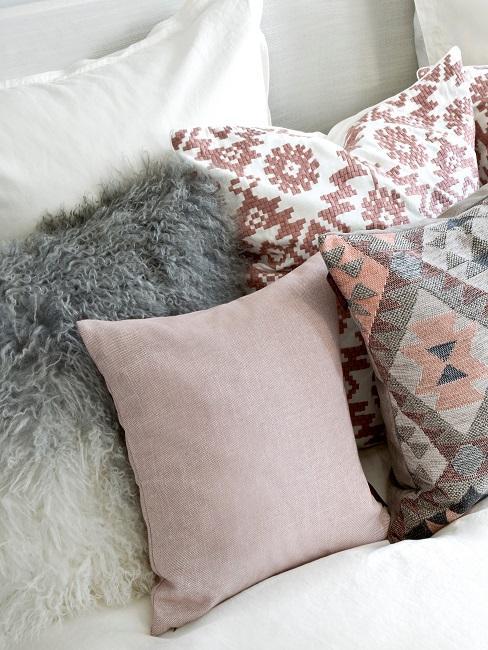 Helles Bett mit einem Kissen im Ombre Look aus Kunstfell, einem in Rosa und zwei gemusterten Boho Kissen
