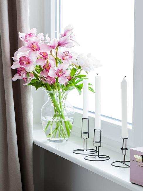 Fensterbank Deko mit Blumen und Kerzen.