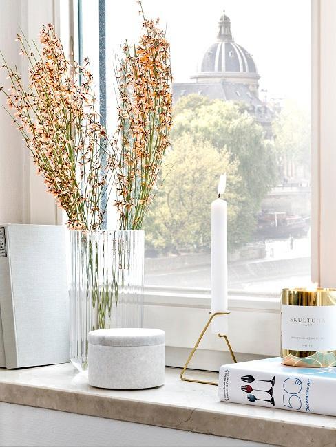 Fensterbank Deko herbstlich mit einer Kerze, einer Dose, Büchern und einer Vase.