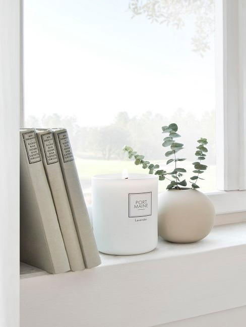 Fensterbank Deko mit einer Kerze, einer kleinen Vase und Deko Büchern.