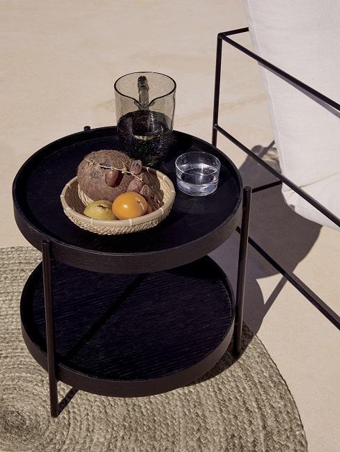Holzschale dekorieren im Sommer mit Kokosnuss und Mandarine auf schwarzem Beistelltisch