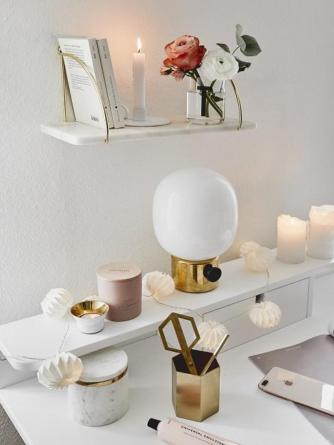 Schreibtisch mit Utensilien sowie schöner Deko durch Kerzen, Blumen und einer Lichterkette
