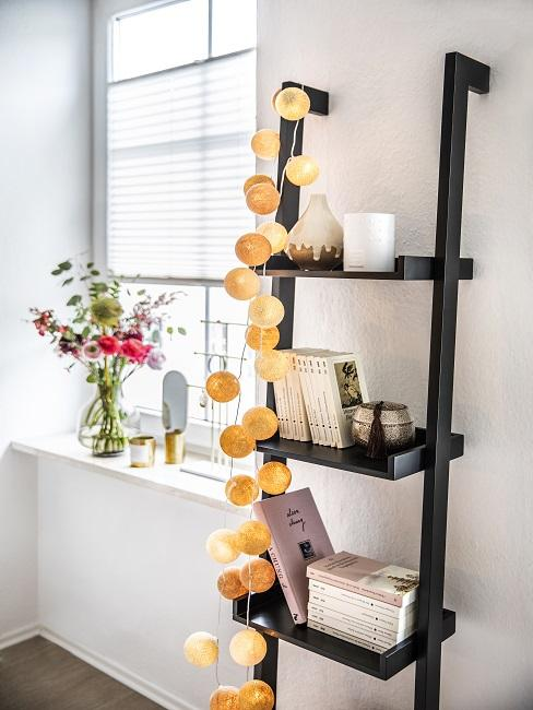 Ladder shelf with books and a string of lights next to the window