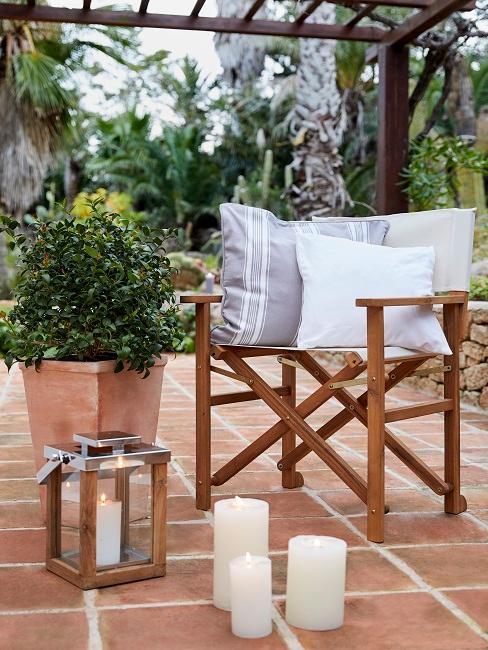 Gartenstuhl neben Dekoelementen auf einer Terasse