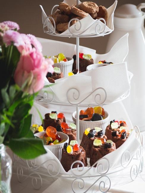 Ein Etagere mit Schokomuffins und Keksen uf einem Buffet neben Blumen