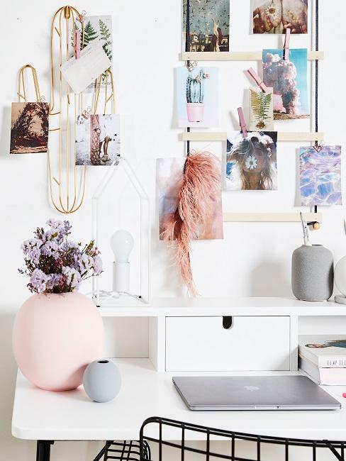 Vision Board mit Fotos hängt an der Wand über dem Schreibtisch.