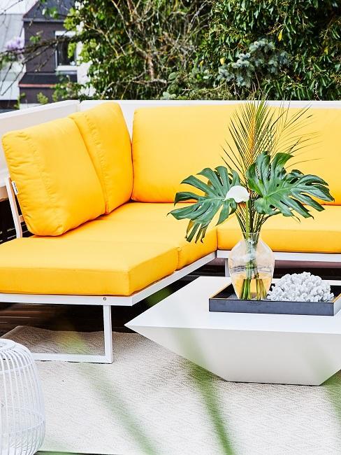 Terrasse mit einer Loungeecke mit gelben Polstern.