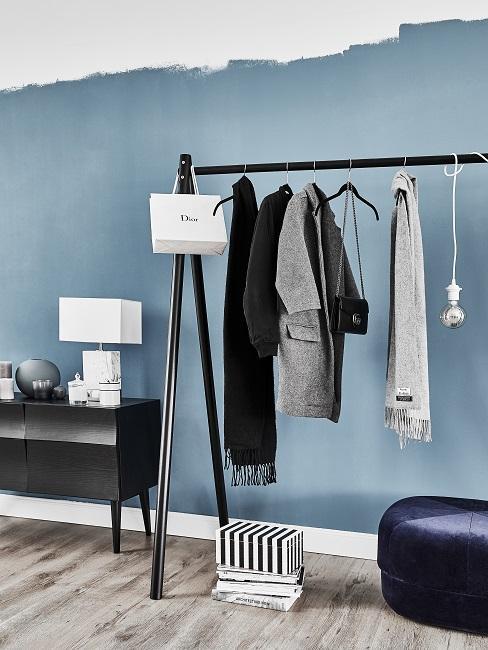 Eine blaue Wand im Flur mit einer Garderobe, daneben ein Sideboard mit Lampe und Deko