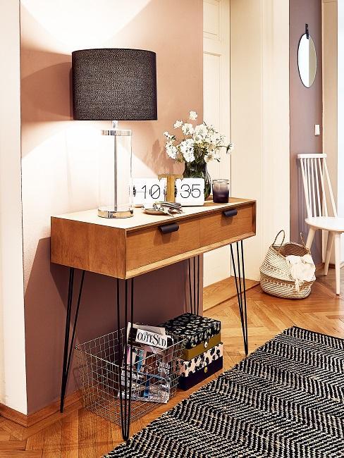 Eine Holzkonsole mit reichlich Deko vor einer Wand in Altrosa, davor ein Muster-Teppich