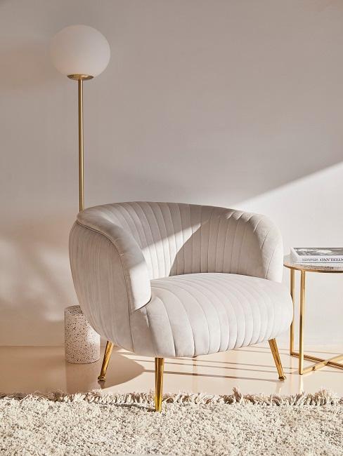 Heller Raum in Weißtönen mit Goldakzenten mit Sessel, einer Stehlampe, einem Teppich und einem kleinen Beistelltisch