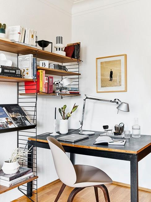 Arbeitsplatz mit moderner Einrichtung: Einem Schreibtisch in Schwarz mit puristischer Deko und einem String Regal mit Büchern