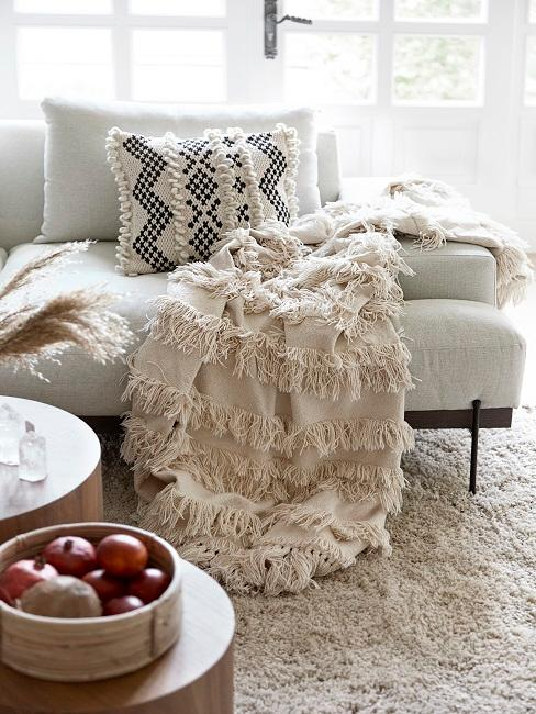 Helles Sofa mit einem Kissen mit Ethno Muster und einem Plaid mit Fransen in beige sowie einem fransigen Teppich