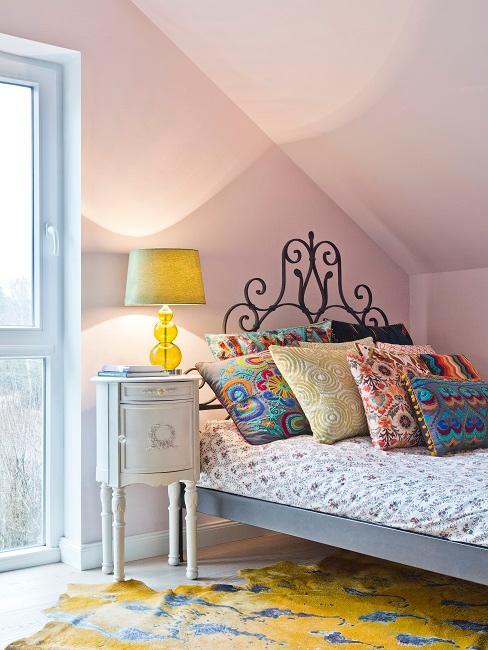 Bett aus verschnörkeltem Metall mit vielen bunten Boho Kissen und einem Boho Teppich in Gelb mit Muster daneben