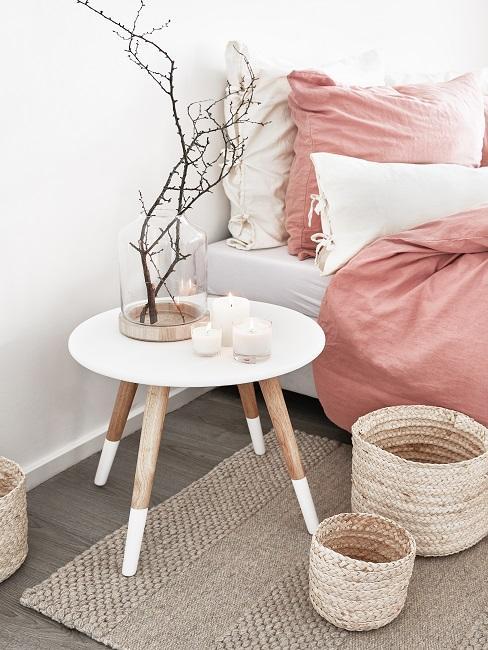 Bett in Rosa-Weiß, daneben ein weißer Beistelltisch auf einem Jute Teppich mit Aufbewahrungskörben