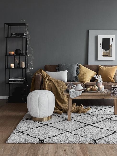 Gedeckte Farben Wohnzimmer mit grauer Wand, Ledercouch, gelben und grauen Kissen, Samthocker in weiß und kariertem Teppich