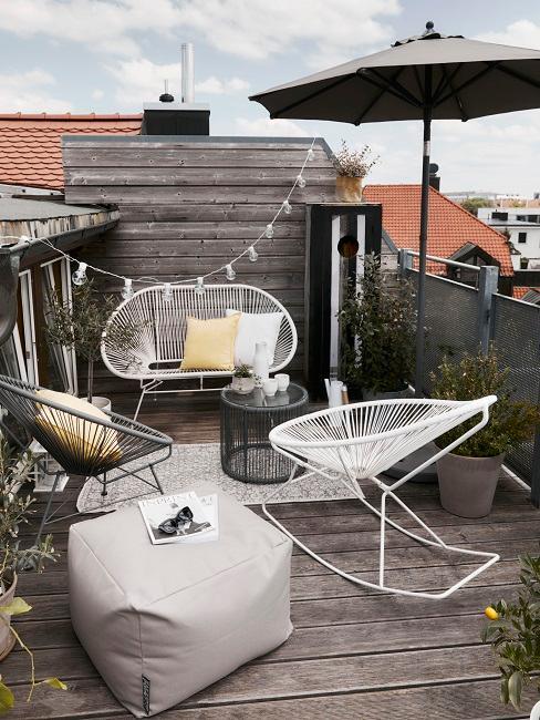 Kleiner Balkon mit Acapulco-Stühlen, grauem Sitzpouf, Lichterkette und gelben und weißen Kissen