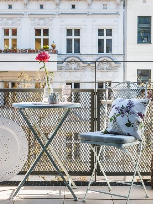 Kleiner Balkon mit Metallgeländer, einem kleinen Tisch und Stuhl sowie einem Kissen und einer Vase als Deko