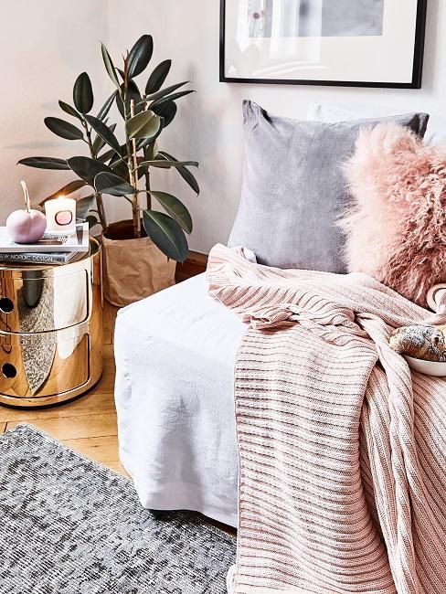 Pflegeleichte Zimmerpflanzen Gummibaum neben silberfarbenen Beistelltisch und Schlafsofa mit rosa und grauen Kissen