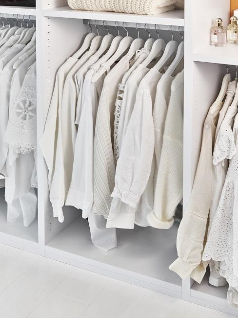 Begehbarer Kleiderschrank Kleiderstange mit vielen weißen Blusen auf Kleiderbügeln