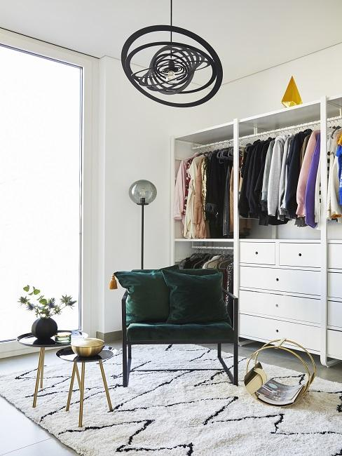 Begehbarer Kleiderschrank Sessel auf Teppich neben kleinem Beistelltisch und Schrank