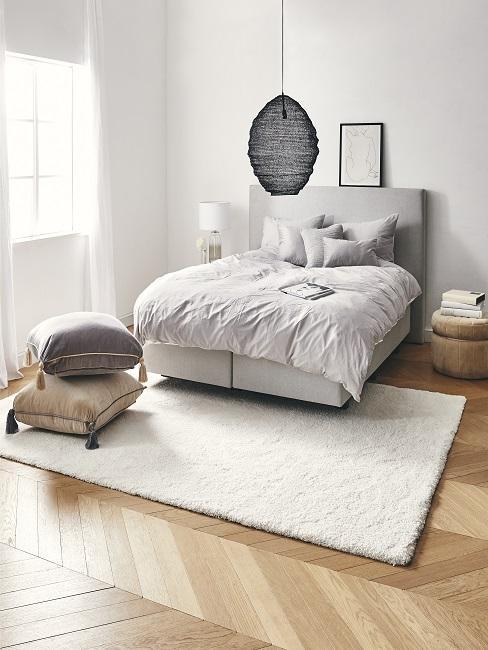 Helles Schlafzimmer mit einem Luxus-Boxspringbett, eiinem Teppich und einer stylischen Pendelleuchte