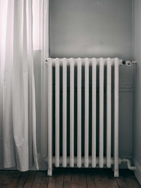 Schmale Heizung neben einem Fenster mit zugezogenem Vorhang