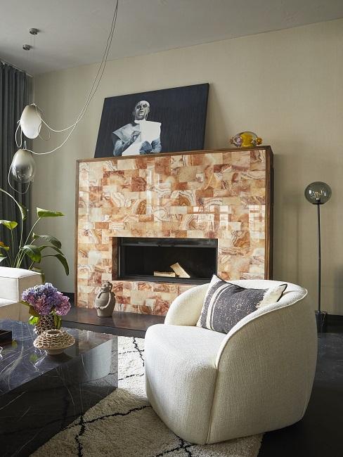 Wohnzimmer mit Sofa, Sessel und Couchtisch vor einem Kamin zum Heizen
