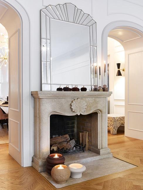 Helles Wohnzimmer mit Fischgrät-Parkett und einem edlen Kamin zum Heizen mit großen Kerzen davor