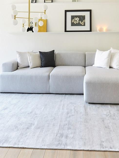 Großes graues Sofa auf großem Teppich