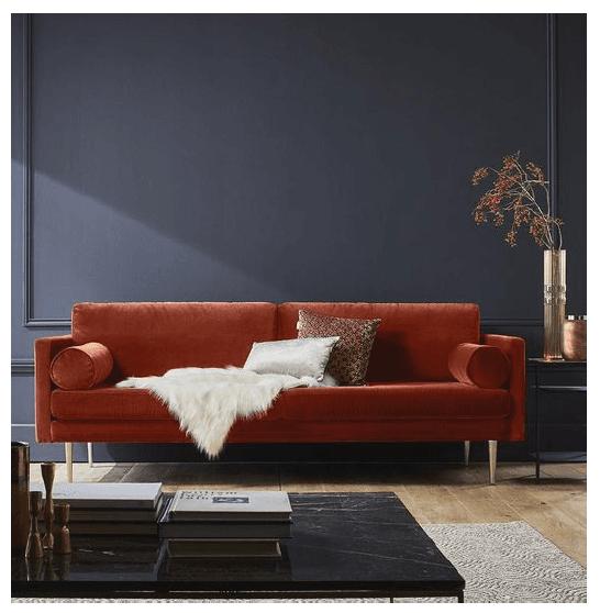 Rostrotes Sofa in dunklem Wohnzimmer