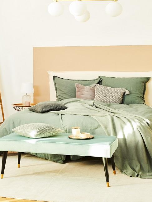 Doppelbett mit grüner Bettwäsche und Sitzbank davor